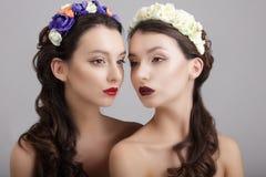 inspiration Zwei redeten Frauen mit Kränzen von Blumen an Stockfotografie