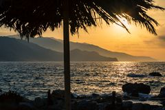 Inspirational beautiful sunrise landscape at sea and mountains. Inspirational beautiful mountains landscape with palm tree at sea, coast, beach and rocks, high royalty free stock photos