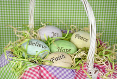 Inspirational Easter Eggs. Inspirational words on pastel Easter eggs in white wicker basket with gingham fabric Stock Image