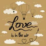 Inspirational hand getrokken uitdrukkingsliefde is in de lucht verfraaide hete ballon, harten, pijl, hemel, wolken Stock Afbeeldingen
