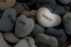 Inspirational heart shaped stones in basket. Small heart shaped gray stones with inspirational mantras such as peace smile blessing love bloom friend breathe stock photos