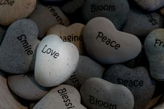 Inspirational heart shaped stones in basket. Small heart shaped gray stones with inspirational mantras such as peace smile blessing love bloom friend breathe stock photography