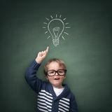 Inspirational idea. Schoolboy standing in front of a blackboard with a bright idea light bulb above his head concept for innovation, imagination and Royalty Free Stock Photography