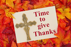 An inspirational message. Some fall leaves with a blank beige greeting card with a cross with text Time to give Thanks stock photo