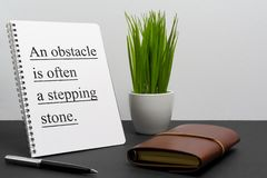 Inspirational and motivation life and business quote on notepad. An Obstacle is Often a Stepping Stone royalty free stock photography