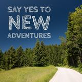 Inspirational motivation quote on natural landscape background, say yes to new adventures. Positive attitude concept royalty free stock images