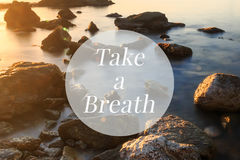 Inspirational motivation quote, take a breath. On a sea shore in sunset background stock photos