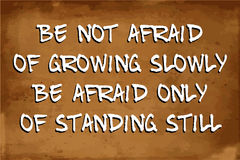 Inspirational motivational quote. – Be not afraid of growing slowly Be afraid only of standing still – quote on blurred vintage grunge background Royalty Free Stock Images
