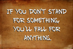 Inspirational motivational quote. – If you don`t stand for something, you`ll fall for anything – quote on blurred vintage grunge background Stock Images