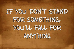 Inspirational motivational quote. – If you don`t stand for something, you`ll fall for anything – quote on blurred vintage grunge background Stock Photos