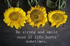 Free Inspirational Motivational Quote - Be Strong And Smile Even If Life Hurts Sometimes. With Yellow Sun Flowers Decoration On Rustic Stock Photo - 161633870