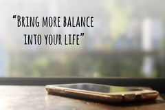 Inspirational quote. Inspirational Motivational quote `being more balance into your life` on blurred cellphone on the desk background Stock Photo