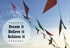 Inspirational quote. Inspirational Motivational quote `dream it believe it achieve it on blurred flags background Stock Photo