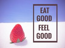 Inspirational Quote. Inspirational Motivational Quote `eat good feel good` on strawberry background Royalty Free Stock Photo