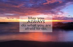 Inspirational motivational quote- May you always do what you are afraid to do. With blurry image of dramatic colorful sky at. Sunset and beautiful beach royalty free stock image