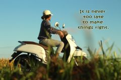 Inspirational motivational quote- It is never too late to make things right. With blurry image of  young woman riding motorbike in stock photography