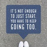 Inspirational motivational quote `it`s not enough to just start, you have to keep going too.`. On top view of feet background stock photos
