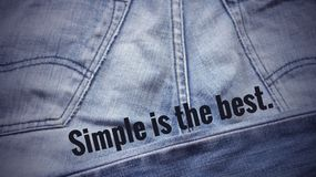 Inspirational quote. Inspirational Motivational quote `simple is the best` on blurred Jeans background with vintage filter Royalty Free Stock Photography