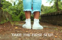 Inspirational motivational quote- Take the first step. With feet of young woman in white sneakers standing from back. Green nature royalty free stock photography