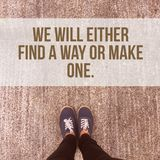 Inspirational motivational quote `we will either find a way or make one.`. On foot standing on concrete floor background Stock Image