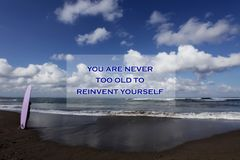 Inspirational motivational quote- You are never too old to reinvent yourself. With blurry image of a young surfer girl standing stock image