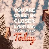 Inspirational motivational quote `you are one step closer everyday, so don`t give up today`. On buildings and sky background Stock Photos