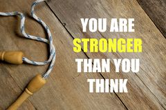 Inspirational motivational quotes You Are Stronger Than You Think on wooden background. Health and fitness concept.
