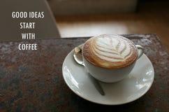 Inspirational positieve citaat` Goede ideeën beginnen met koffie ` met de koffie van de bladvorm latte op de roestige bureauachte Stock Afbeeldingen