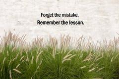 Inspirational positieve citaat ` vergeet de fout, herinnert de les ` op cementachtergrond en de achtergrond van de grasbloem Stock Afbeelding