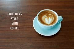 Inspirational positive quote `Good ideas start with coffee` with heart shape latte coffee and wooden desk background. An inspirational positive quote to cheer Stock Image