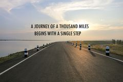 Inspirational positive quote `A journey of a thousand miles begins with a single step` on a road and water reservior background. An inspirational positive quote Stock Photos