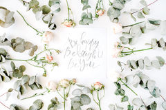 Inspirational quote be happy, be bright, be you written in calligraphy style on paper with pink roses and eucalyptus branches on w Royalty Free Stock Photos