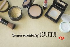 Inspirational quote  `Be your own kind of beautiful`. Inspirational quote `Be your own kind of beautiful` on blurred set of cosmetics background Royalty Free Stock Image