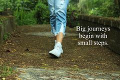 Inspirational quote- Big journeys begin with small steps. With feet of young woman walking surrounding with fresh green nature. Background in the forest royalty free stock photo
