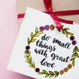Inspirational quote do small things with great love handwritten in calligraphy style. Gift in kraft paper with a red ribbon. Flat. Lay Royalty Free Stock Image