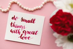 Inspirational quote do small things with great love handwritten in calligraphy style with watercolor. Floral composition on a pale. Pink pastel background Stock Image