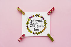 Inspirational quote `do small things with great love` handwritten with watercolor in calligraphy style. Miniature clothespins on a pink background. Flat lay Stock Image