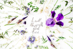 Inspirational quote `do small things with great love` written in calligraphy style on paper with wreath frame with purple iris flo Stock Photo