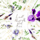 Inspirational quote `do small things with great love` written in calligraphy style on paper with wreath frame with purple iris flo Royalty Free Stock Image