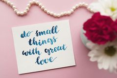 Inspirational quote Do small things with great love written in calligraphy style with watercolor. Composition on a pink background.  Royalty Free Stock Photos