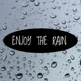 Inspirational quote `enjoy the rain`. On blurred background Royalty Free Stock Photos