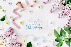 Inspirational quote `everyday is a new adventure` written in calligraphy style on paper with wreath frame with lilac and chamomile. On white background. flat royalty free stock photos