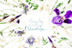 Inspirational quote `everyday is a new adventure` written in calligraphy style on paper with wreath frame with purple iris flower. And lilies isolated on white Stock Photos