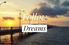 Inspirational quote - Follow your dreams. Blurry sunset background stock image