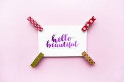 Inspirational quote Hello beautiful handwritten with watercolor in calligraphy style, miniature clothespins on a pink background. Stock Photo