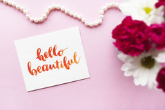 Inspirational quote Hello beautiful written in calligraphy style with watercolor. Composition on a pink background. Flat lay Stock Images