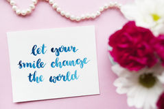 Inspirational quote Let your smile change the world written in calligraphy style with watercolor. Composition on a pink background Royalty Free Stock Photo