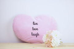 Inspirational quote. `live love laugh` on flowers and heart pillow blurred background with pastel filter Stock Images