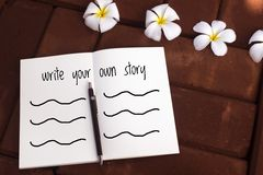 Inspirational quote. Inspirational motivational quote `write your own story` on blurred notebook background Stock Photo