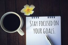 Free Inspirational Quote - Stay Focused On Your Goals. With Text Message On White Paper Book, Pen, A Cup Of Morning Coffee, Flower. Stock Photos - 178719553